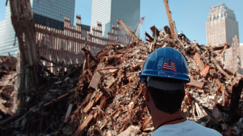 "A worker stands in front of rubble from the World Trade Center at Ground Zero in Lower Manhattan several weeks after the September 11 attacks. ""911: Ground Zero; 10/03/2001."" From Records of the White House Photo Office, via National Archives (Identifier: 5997364)."