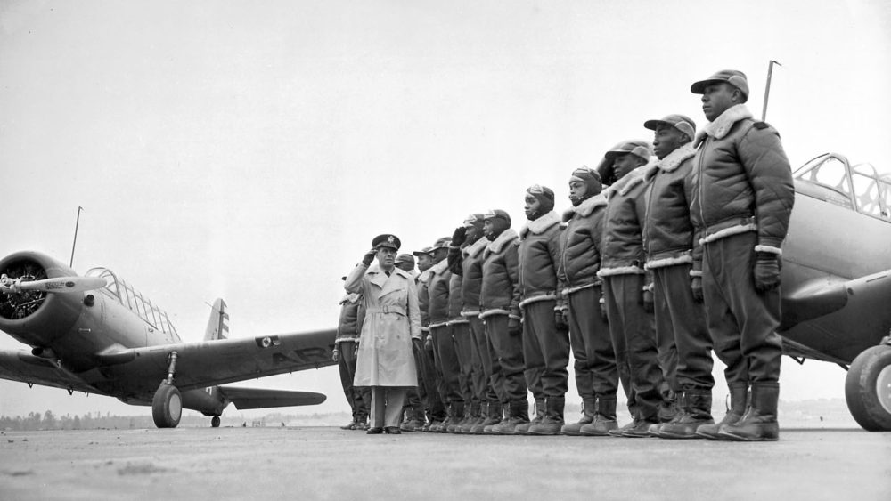 The Tuskegee Airmen stand at attention as Major James A. Ellison returns the salute of Mac Ross, one of the first graduates of the Tuskegee cadets. The photographs shows the pride and poise of the Tuskegee Airmen, who continued a tradition of African Americans honorably serving a country that still considered them second-class citizens. Photograph, 1941. Via Wikimedia.