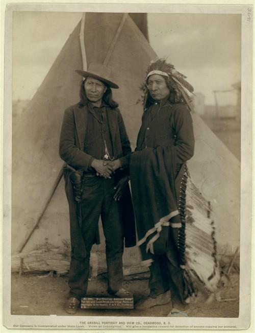 "Red Cloud and American Horse – two of the most renowned Ogala chiefs – are seen clasping hands in front of a tipi on the Pine Ridge Reservation in South Dakota. Both men served as delegates to Washington, D.C., after years of actively fighting the American government. John C. Grabill, ""'Red Cloud and American Horse.' The two most noted chiefs now living,"" 1891. Library of Congress, http://www.loc.gov/pictures/item/99613806/."