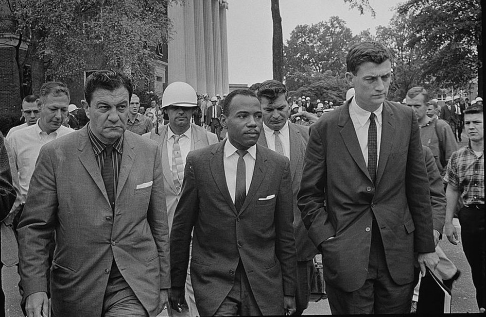 "James Meredith, accompanied by U.S. Marshalls, walks to class at the University of Mississippi in 1962. Meredith was the first African-American student admitted to the still segregated Ole Miss. Marion S. Trikosko, ""Integration at Ole Miss[issippi] Univ[ersity],"" 1962. Library of Congress, http://www.loc.gov/pictures/item/2003688159/."