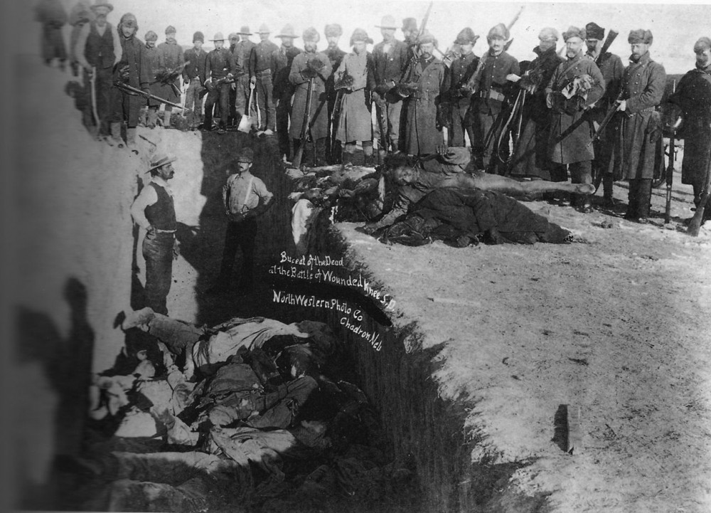 Burial of the dead after the massacre of Wounded Knee. U.S. Soldiers putting Indians in common grave; some corpses are frozen in different positions. South Dakota. 1891. Library of Congress.