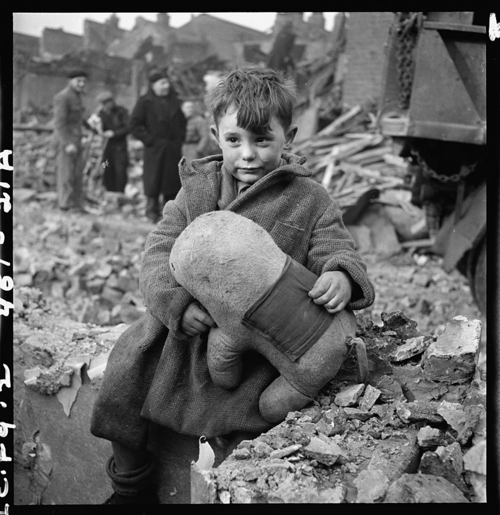"The German aerial bombing of London left thousands homeless, hurt, or dead. This child sits among the rubble with a rather quizzical look on his face, as adults ponder their fate in the background. Toni Frissell, ""[Abandoned boy holding a stuffed toy animal amid ruins following German aerial bombing of London],"" 1945. Library of Congress, http://www.loc.gov/pictures/item/2008680191/."
