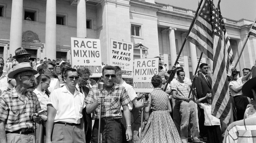 "In 1959, photographer John Bledsoe captured this image of the crowd on the steps of the Arkansas state capitol building, protesting the federally mandated integration of Little Rock's Central High School. This image shows how worries about desegregation were bound up with other concerns, such as the reach of communism and government power. John T. Bledsoe, ""Little Rock, 1959. Rally at State Capitol"" (Aug 20, 1959). Via Library of Congress. John T. Bledsoe, ""Little Rock, 1959. Rally at State Capitol"" (Aug 20, 1959). Via Library of Congress."
