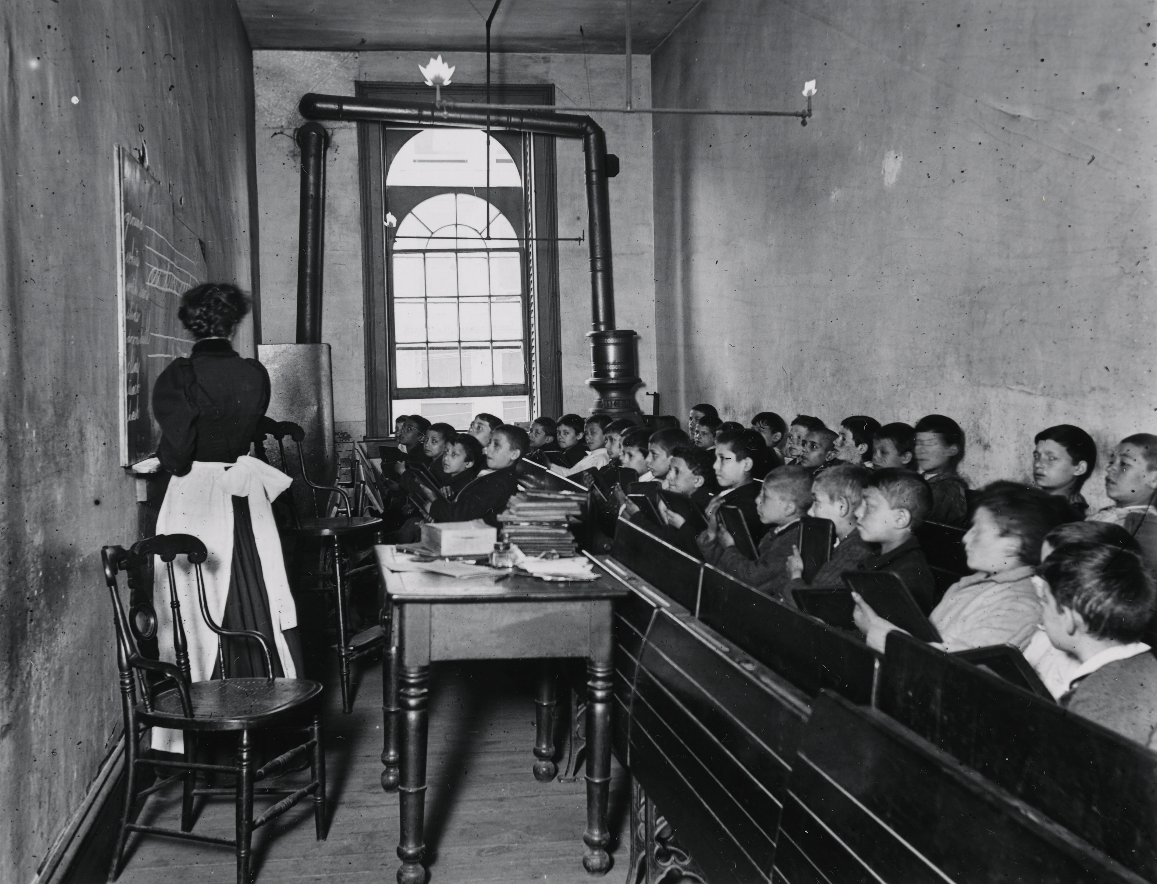"""A Class in the Condemned Essex Market School, With the Gas Burning by Day."" Via Preus Museum"