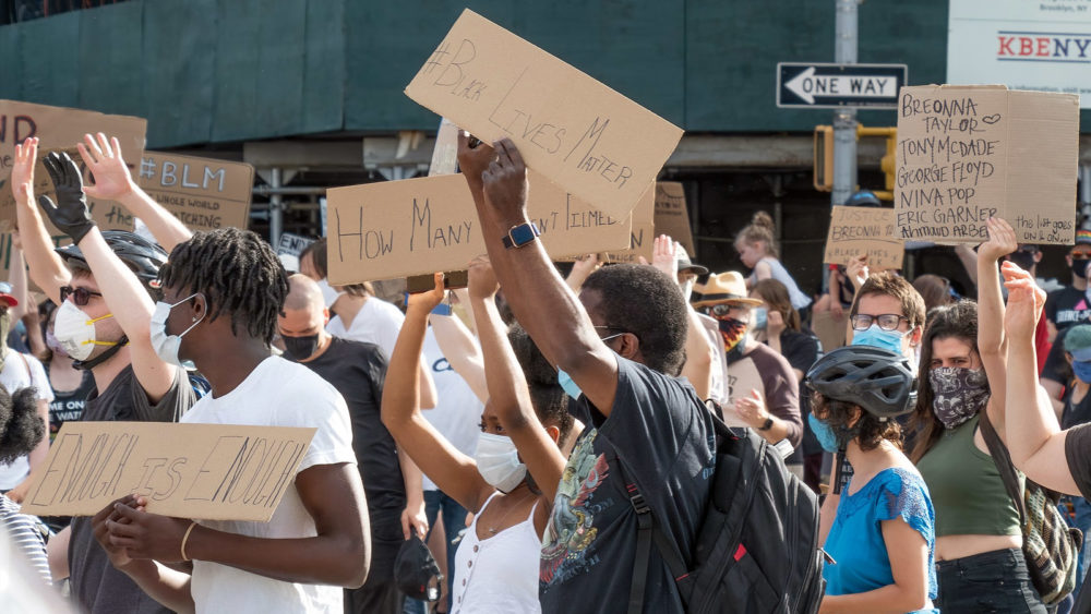 """Crowds, holding homemade signs reading """"Black Lives Matter"""" and """"Enough is Enough,"""" march in New York City."""