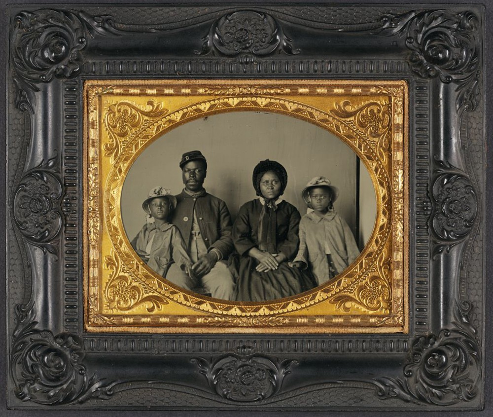 "This African American family dressed in their finest clothes (including a USCT uniform) for this photograph, projecting respectability and dignity that was at odds with the southern perception of black Americans. ""[Unidentified African American soldier in Union uniform with wife and two daughters],"" between 1863 and 1865. Library of Congress, http://www.loc.gov/pictures/item/2010647216/."