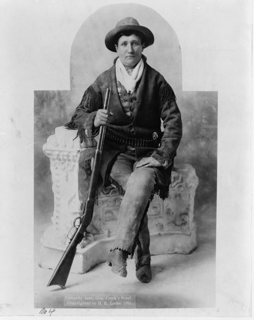 "American frontierswoman and professional scout Martha Jane Canary was better known to America as Calamity Jane. A figure in western folklore during her life and after, Calamity Jane was a central character in many of the increasingly popular novels and films that romanticized western life in the twentieth century. ""[Martha Canary, 1852-1903, (""Calamity Jane""), full-length portrait, seated with rifle as General Crook's scout],"" c. 1895. Library of Congress, http://www.loc.gov/pictures/item/2005689345/."