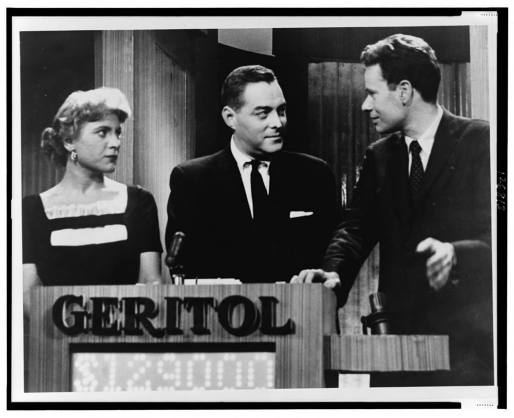 "Advertising began creeping up everywhere in the 1950s. No longer confined to commercials or newspapers, advertisements were subtly (or not so subtly in this case) worked into TV shows like the Quiz Show ""21"". (Geritol is a dietary supplement.) Orlando Fernandez, ""[Quiz show ""21"" host Jack Barry turns toward contestant Charles Van Doren as fellow contestant Vivienne Nearine looks on],"" 1957. Library of Congress, http://www.loc.gov/pictures/item/00652124/."