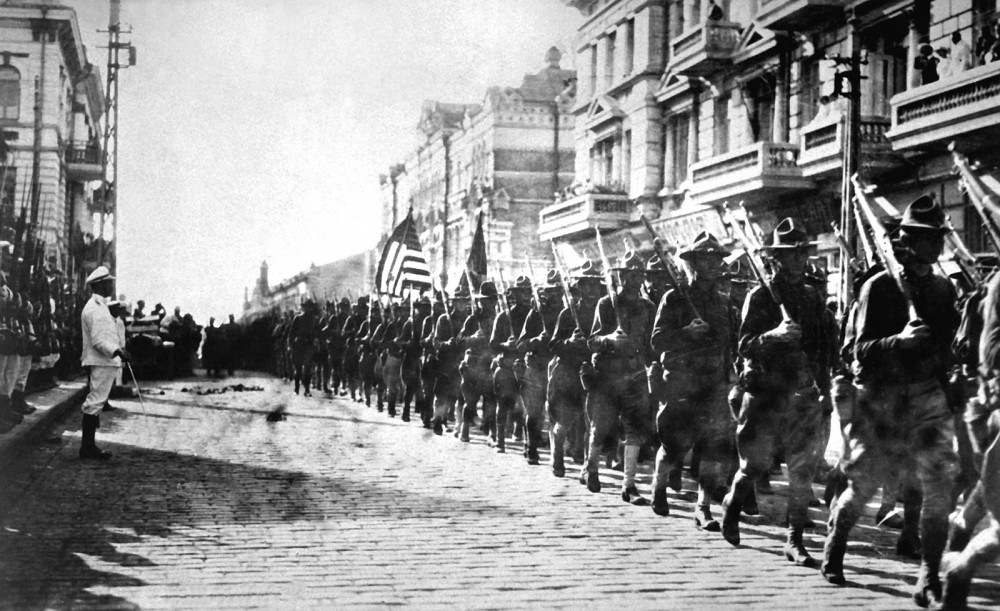 While still fighting in WWI, President Wilson sent American troops to Siberia during the Russian Civil War for reasons both diplomatic and military. This photograph shows American soldiers in Vladivostok parading before the building occupied by the staff of the Czecho-Slovaks (those opposing the Bolsheviks). To the left, Japanese marines stand to attention as the American troops march. Photograph, August 1, 1918. Wikimedia, http://commons.wikimedia.org/wiki/File:American_troops_in_Vladivostok_1918_HD-SN-99-02013.JPEG.