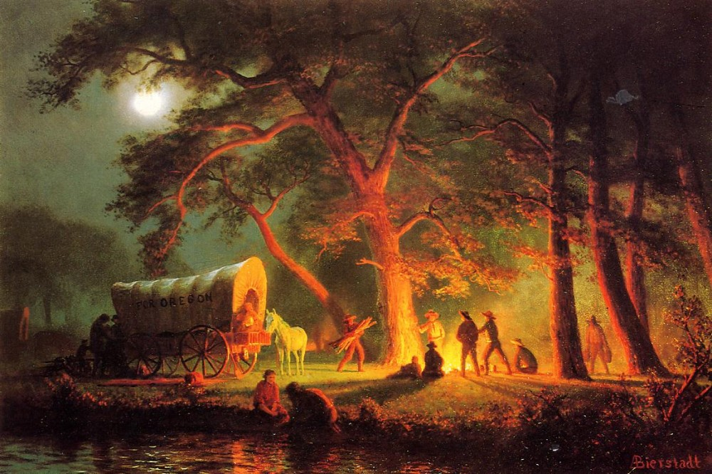 A group of people and a covered wagon by a fire in the middle of the woods at night.