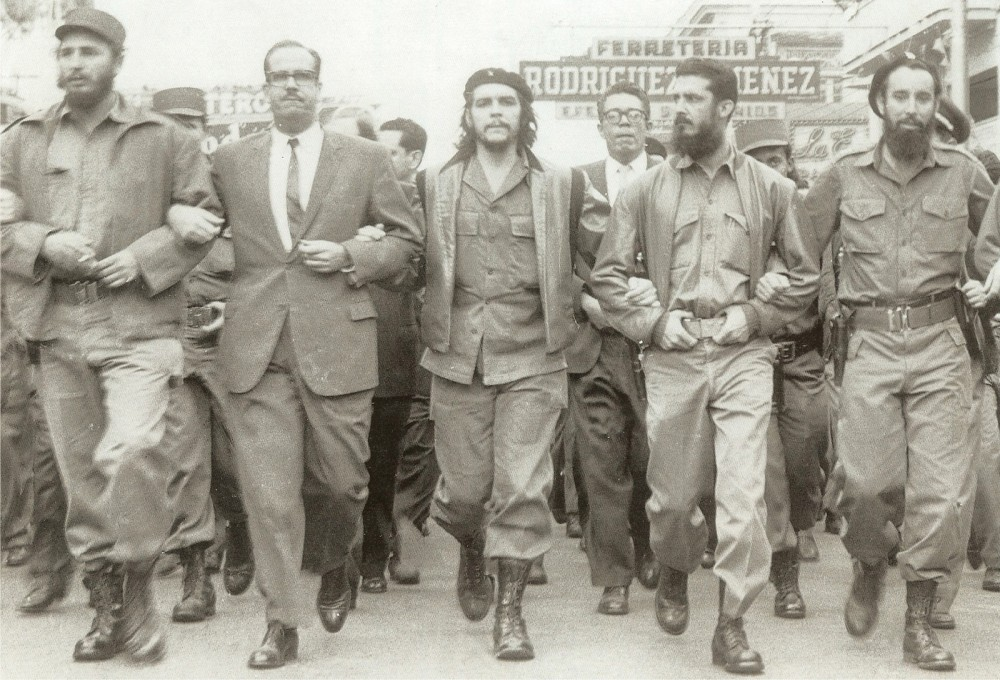Photograph of revolutionaries, including Che Guevara and Fidel Castro, marching arm and arm.