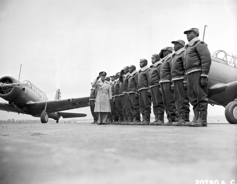 The Tuskegee Airmen stand at attention as Major James A. Ellison returns the salute of Mac Ross, one of the first graduates of the Tuskegee cadets. The photographs shows the pride and poise of the Tuskegee Airmen, who continued a tradition of African Americans honorably serving a country that still considered them second-class citizens. Photograph, 1941. Wikimedia, http://commons.wikimedia.org/wiki/File:First_Tuskeegee_Class.jpg.