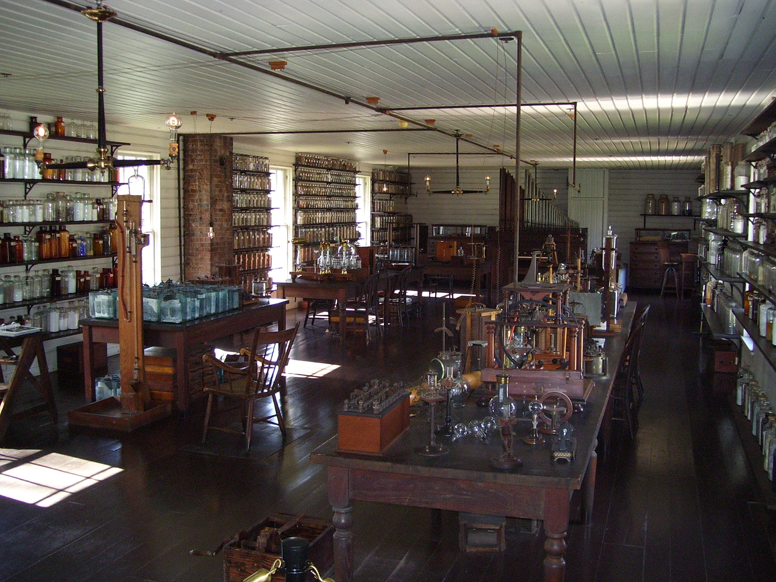 A laboratory with tables full of glass containers and shelves full of glass containers.