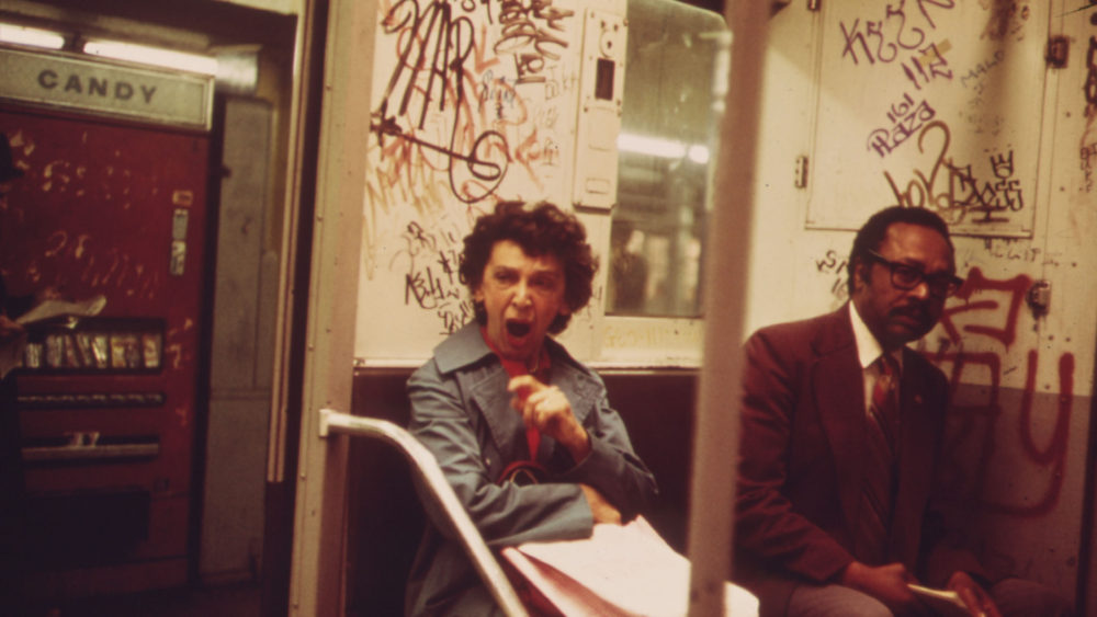 """Urban Decay"" confronted Americans of the 1960s and 1970s. As the economy sagged and deindustrialization hit much of the country, many Americans associated major cities with poverty and crime. In this 1973 photo, two subway riders sit amid a graffitied subway car in New York City. Erik Calonius, ""Many Subway Cars in New York City Have Been Spray-Painted by Vandals"" 1973. Via National Archives (8464439)."