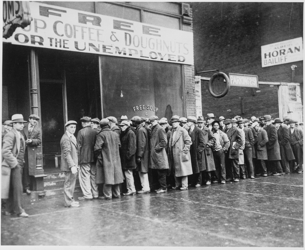 """Unemployed men queued outside a depression soup kitchen opened in Chicago by Al Capone,"" February 1931. Wikimedia, http://commons.wikimedia.org/wiki/File:Unemployed_men_queued_outside_a_depression_soup_kitchen_opened_in_Chicago_by_Al_Capone,_02-1931_-_NARA_-_541927.jpg."