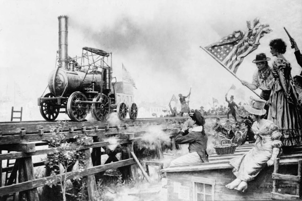 People wave an American flag as they watch a train engine move along tracks.