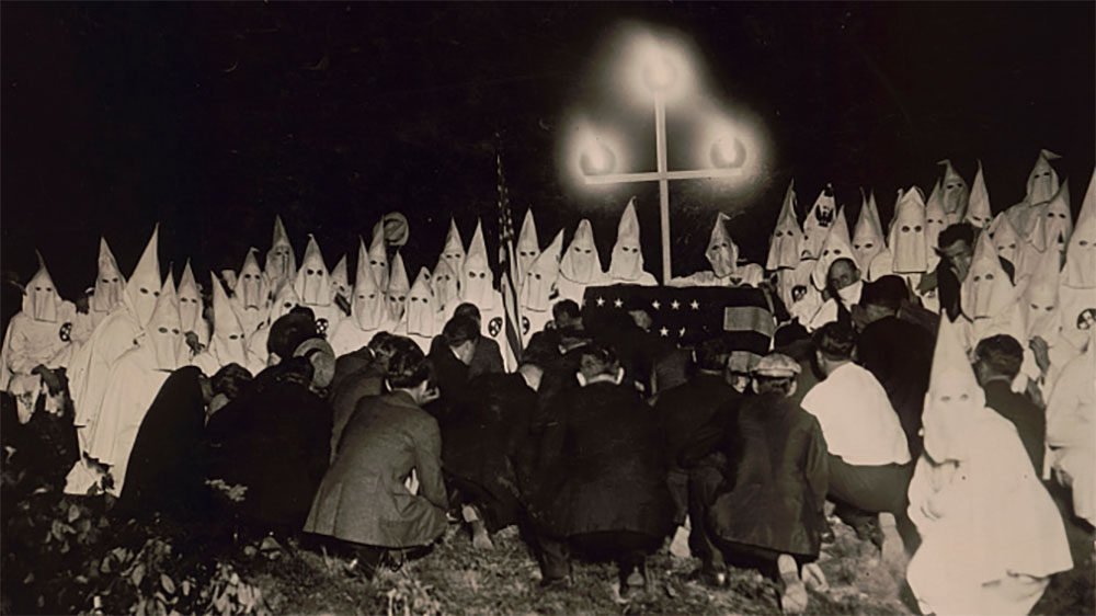 """This photo by popular news photographers Underwood and Underwood shows a gathering of a reported 300 Ku Klux Klansmen just outside Washington DC to initiate a new group of men into their order. The proximity of the photographer to his subjects for one of the Klan's notorious night-time rituals suggests that this was yet another of the Klan's numerous publicity stunts. Underwood and Underwood, """"Klan assembles Short Distance from U.S. Capitol,"""" (ca. 1920's). Library of Congress."""