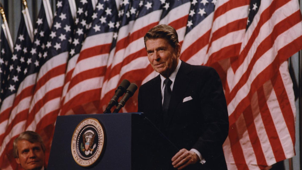 """President Ronald Reagan, a master of the """"photo op,"""" appears here with a row of American flags at his back at a 1982 rally for Senator David Durenberger in Minneapolis, Minnesota. Via National Archives (198527)."""