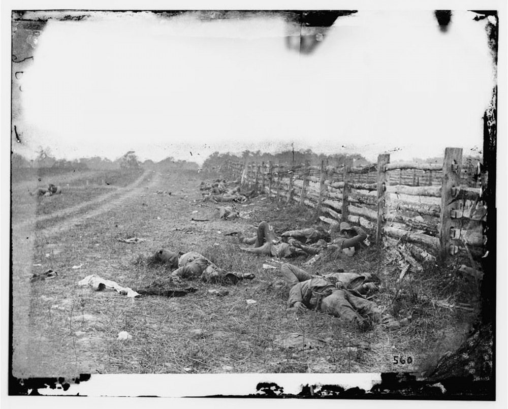 """The relatively new technology of photography captured the horrors of war in realistic ways never before encountered by the American people. Ironically, most photographers arranged the actors in their frames to capture the best picture. They even repositioned bodies of dead soldiers for battlefield photos, rearranging reality to make the most aesthetically pleasing image. Alexander Gardner, """"[Antietam, Md. Confederate dead by a fence on the Hagerstown road],"""" September 1862. Library of Congress, http://www.loc.gov/pictures/item/cwp2003000131/PP/."""