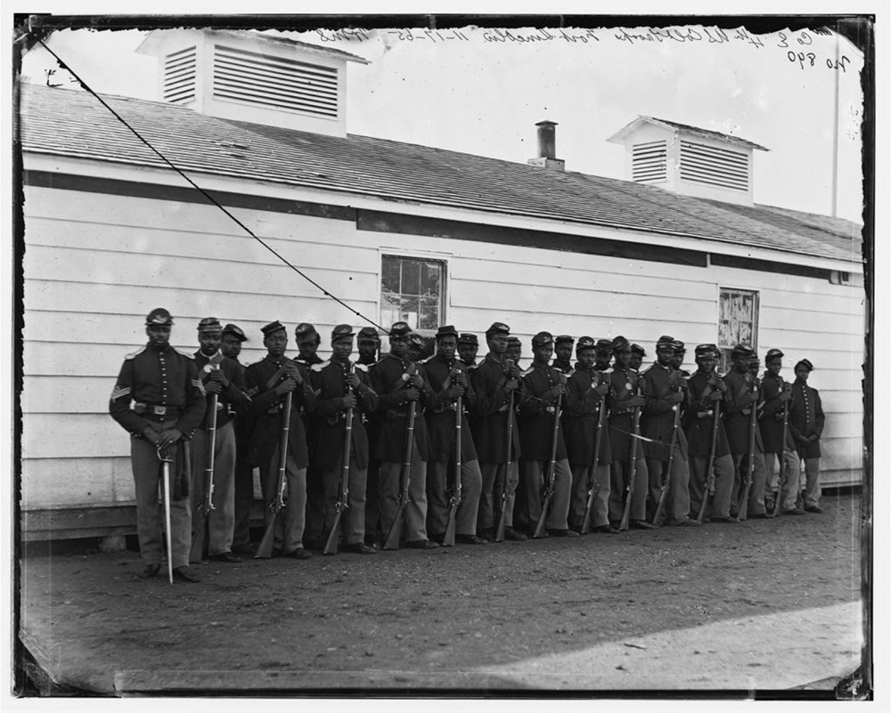 This photograph shows a group of Black soldiers, standing at ease in uniform with their rifles.