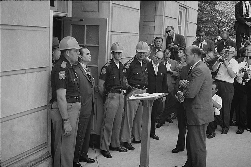 "Alabama governor George Wallace stands defiantly at the door of the University of Alabama, blocking the attempted integration of the school. Wallace was perhaps the most notoriously pro-segregation politician of the 1960s, proudly proclaiming in his 1963 inaugural address ""segregation now, segregation tomorrow, segregation forever."" Warren K. Leffler, ""[Governor George Wallace attempting to block integration at the University of Alabama],"" June 11, 1963. Library of Congress, http://www.loc.gov/pictures/item/2003688161/."