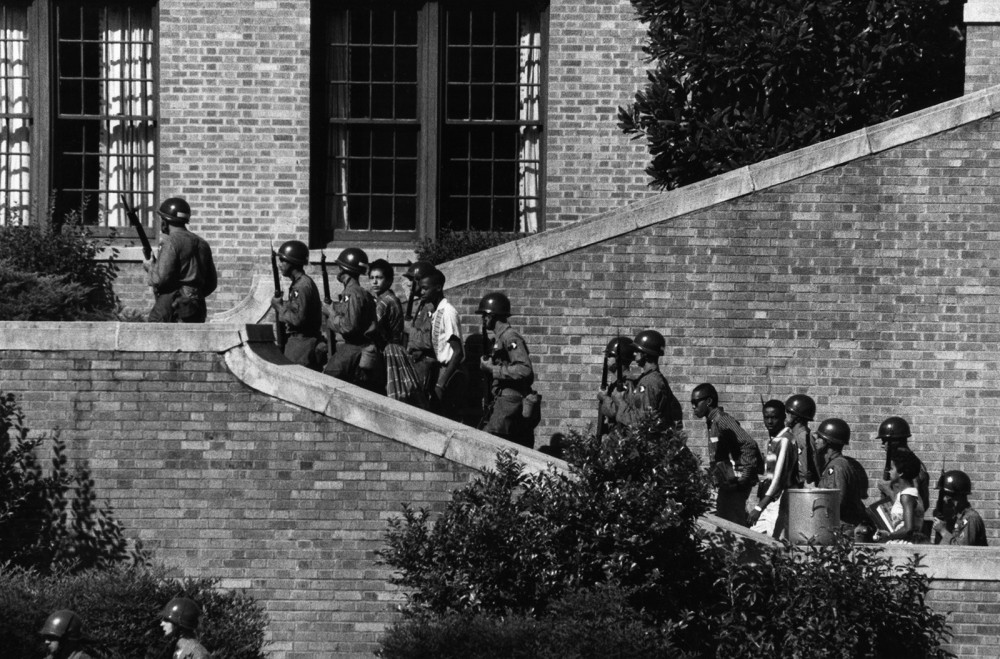 "School desegregation was a tense experience for all involved, but none more so than the African American students brought into white schools. The ""Little Rock Nine"" were the first to do this in Arkansas; their escorts, the 101st Airborne Division of the U.S. Army, provided protection to these students who so bravely took that first step. Photograph, 1957. Wikimedia, http://commons.wikimedia.org/wiki/File:101st_Airborne_at_Little_Rock_Central_High.jpg."