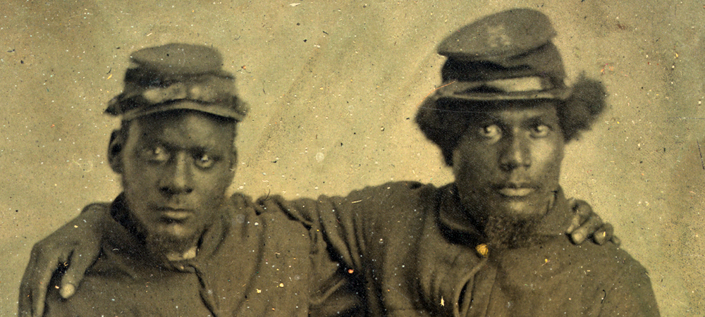 This photograph shows two Black soldiers in uniform, with their arms around one another.