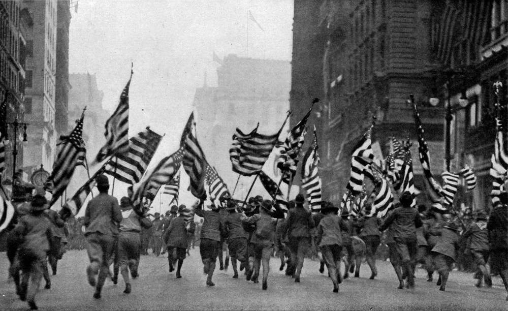 "Moments like this – with the Boy Scouts of America charging up Fifth Avenue in New York City with flags in their hands – signaled to Americans that it was time to wake up to the reality of war and support the effort in any way possible. ""Wake Up, America"" parades like this one were throughout the country in support of recruitment. Nearly 60,000 people attended this single parade in New York City. Photograph from National Geographics Magazine, 1917. Wikimedia, http://commons.wikimedia.org/wiki/File:Boy_Scouts_NGM-v31-p359.jpg."