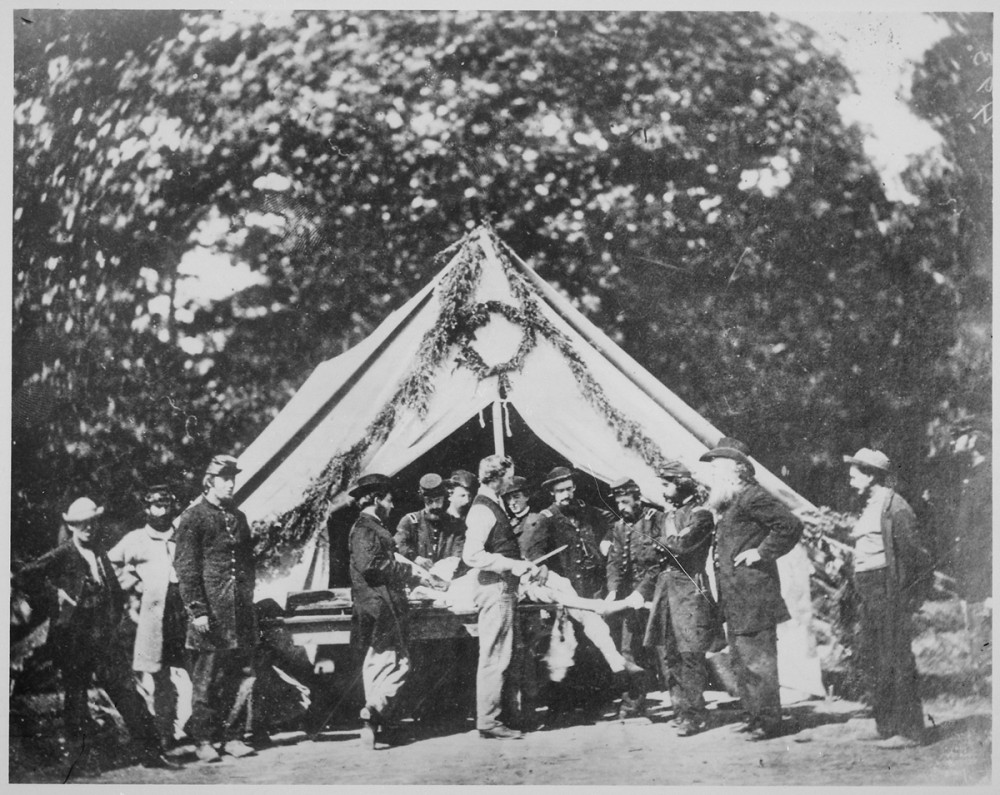 This photograph shows an amputation table in front of a medical tent.