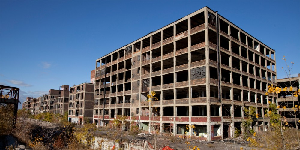 Photograph of an abandoned Packard Automotive Plant in Detroit, Michigan. Via Wikimedia.