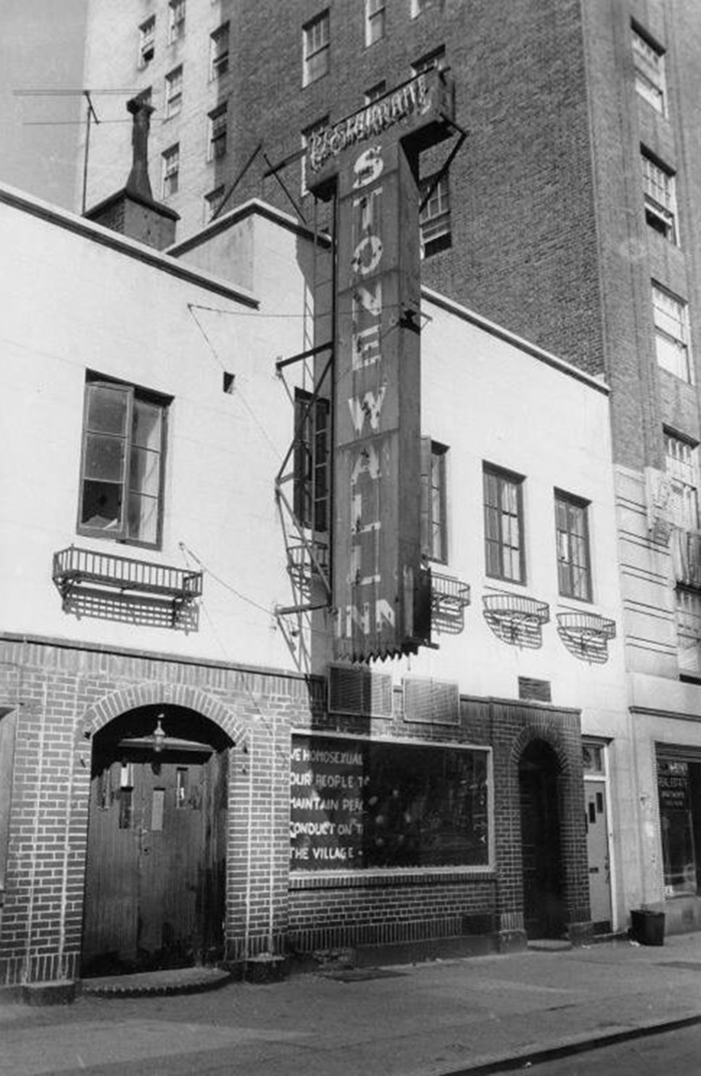 """Photograph of the window under the Stonewall sign that reads: """"We homosexuals plead with our people to please help maintain peaceful and quiet conduct on the streets of the Village--Mattachine."""""""