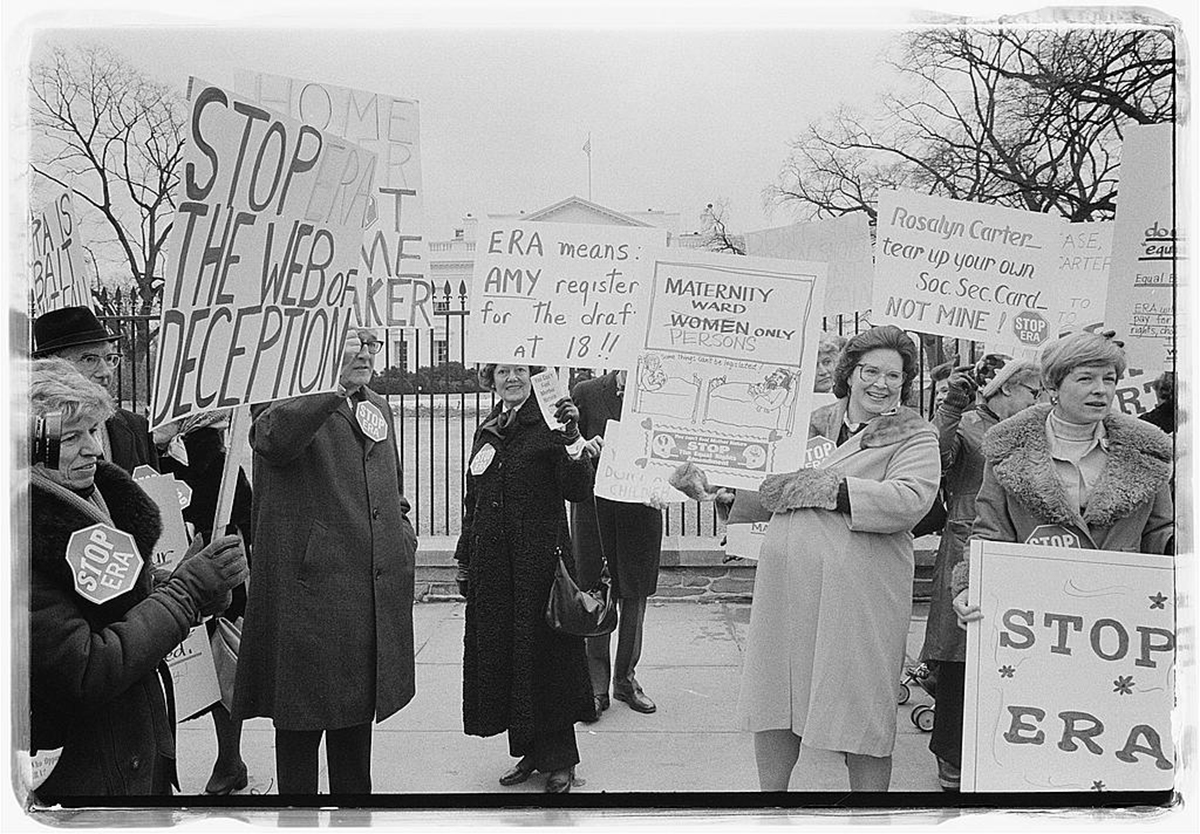 """Photograph of activists opposed to the Equal Rights Amendment standing in front of the White House. Signs say """"Stop the Web of Deception,"""" """"ERA means AMY registers for the draft at 18,"""" """"Maternity Ward Persons (Women is crossed out) Only,"""" and """"Rosalyn Carter tear up your own social security card, not mine!"""""""