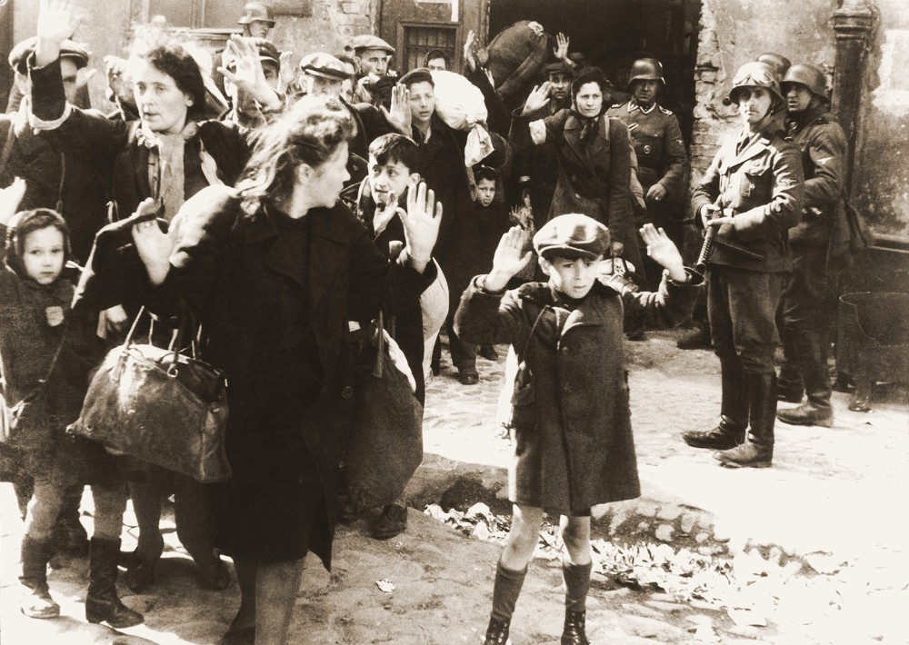 "This photograph became one of the most well-known images from WWII. Originally from Jürgen Stroop's May 1943 report to Heinrich Himmler, it circulated throughout Europe and America as an image of the Nazi Party's brutality. The original German caption read: ""Forcibly pulled out of dug-outs"". Wikimedia, http://commons.wikimedia.org/wiki/File:Stroop_Report_-_Warsaw_Ghetto_Uprising_06b.jpg."