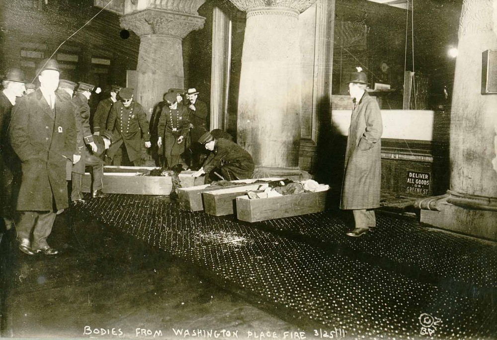 "Photographs like this one made real the potential atrocities resulting from unsafe working conditions, as policemen place the bodies of workers burnt alive in the 1911 Triangle Shirtwaist fire into coffins. ""Bodies from Washington Place fire, Mar 1911,"" March 25, 1911. Library of Congress, http://www.loc.gov/pictures/item/98502780/."