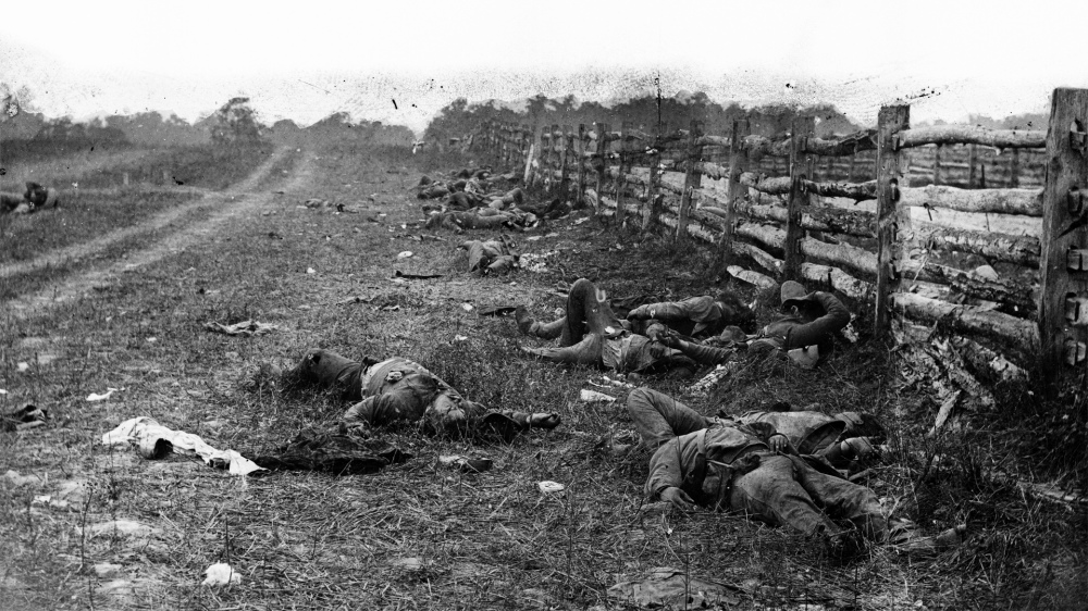 """Photography captured the horrors of war as never before. SomeCivil War photographers arranged the actors in their frames to capture the best picture, even repositioning bodies of dead soldiers for battlefield photos. Alexander Gardner, """"[Antietam, Md. Confederate dead by a fence on the Hagerstown road],"""" September 1862. Library of Congress."""