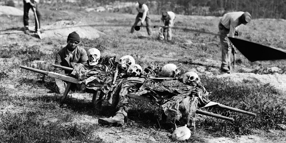 This photograph shows a Black man squatting near a collection of bones and other remains of the war dead.