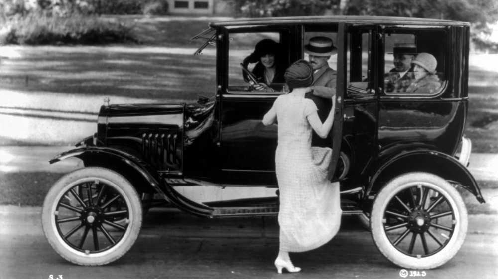 Side view of a Ford sedan with four passengers and a woman getting in on the driver's side, ca.1923. Library of Congress, LC-USZ62-54096.