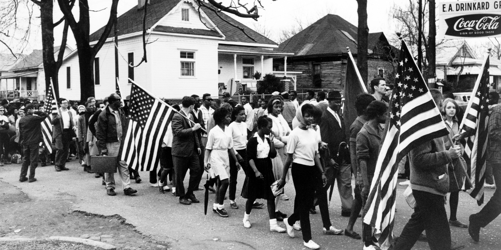 """""""Participants, some carrying American flags, marching in the civil rights march from Selma to Montgomery, Alabama in 1965,"""" via Library of Congress."""